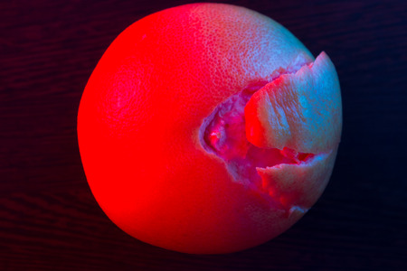 Fresh Red Grapefruit in neon light. dark background