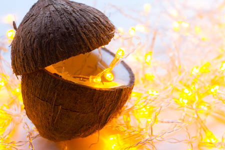 one coconut on the table. garland with yellow light Фото со стока