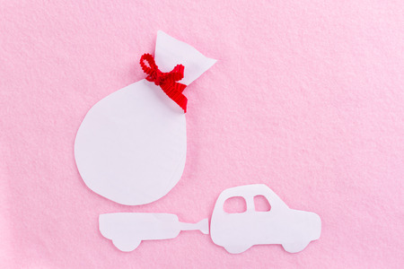 paper car carrying gifts on pink backgrund