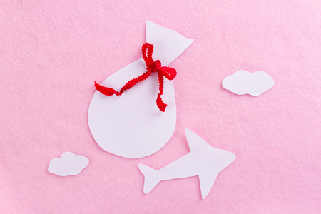 paper airplane carrying presents on pink background