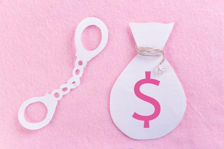 woman criminal concept. hand cuffs on pink bacground