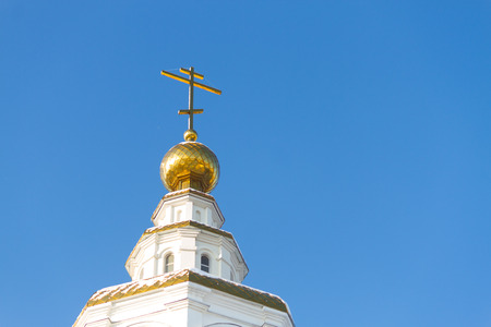 Three domes with crosses of the Orthodox Church, blue sky.