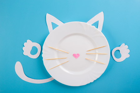 white plate on blue background with funny cat character Standard-Bild - 124940697