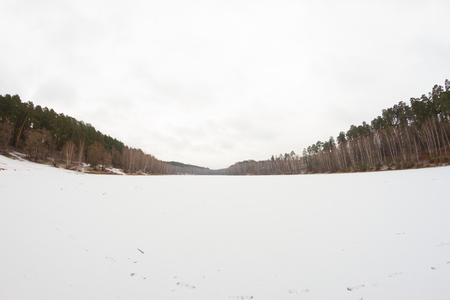 moody landscape with winter frozen lake. grey color
