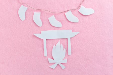 Burning fireplace made of paper. pink background
