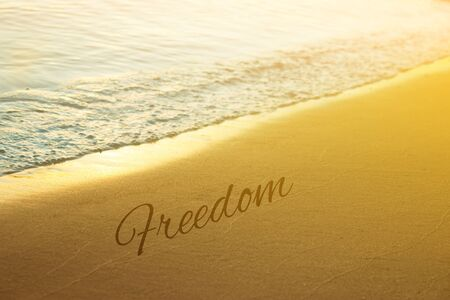 Sunset and Gentle Surf. Freedom word written on sand Imagens