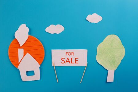 Country house for sale. Paper house on blue background