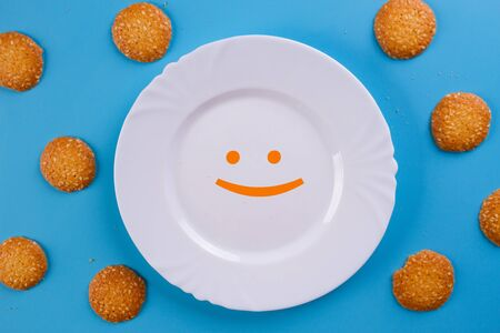 Plate with cookie and funny smile. Blue background