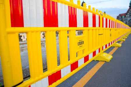 Yellow construction border in the city. Close up