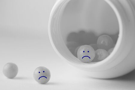 Depression cure pills with funny smiles. Copy space