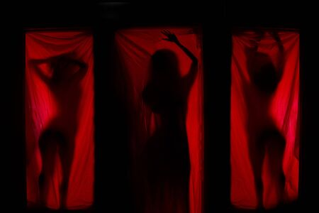 Woman behind red curtains. Prostitute or