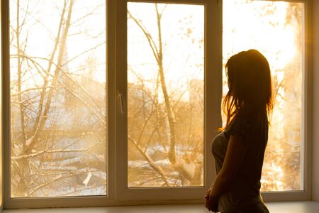 Silhouette of a woman near window. Early morning. Sunrise Фото со стока