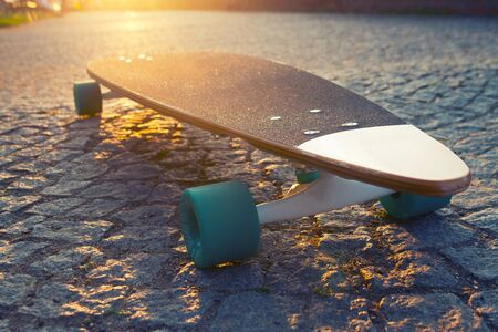 black longboard on the street. Sunny summer day Stock Photo