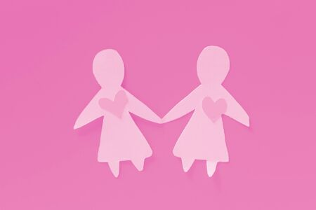 Lesbian concept image. Paper women on pink background