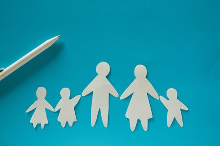Paper family on blue background with copy space
