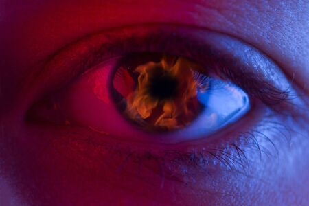 Flame in woman eye. halloween concept image