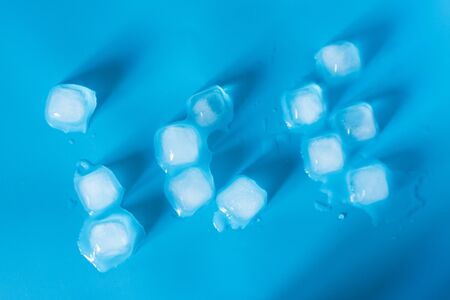 Melting ice cubes background on blue background