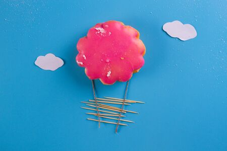pink cookie as airballoon on blue background Stock Photo