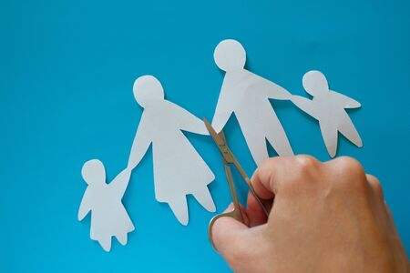 Divorced paper family couple with childrent. Blue background Stock Photo