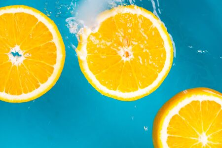 Orange fruits fall deeply under water with splashes