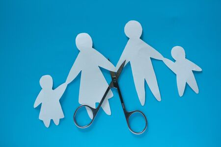 Divorced paper family couple with childrent. Blue background Foto de archivo