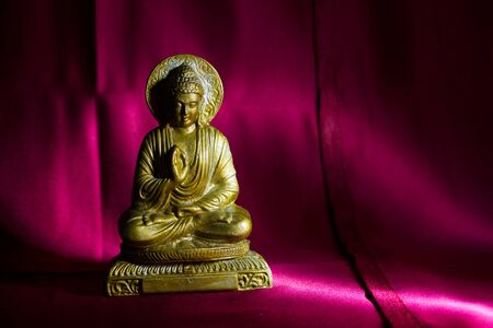 Bronze colored figurine of Buddha. Copy space