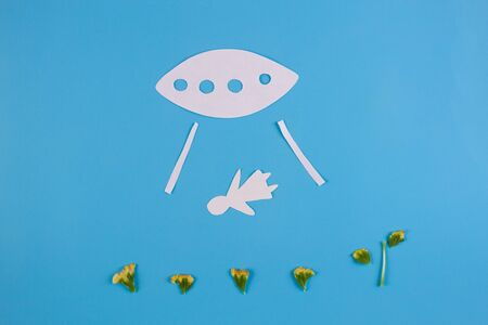 UFO kidnapping person concept. Paper cut on blue background 写真素材