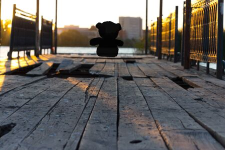 Lonely teddy bear sitting on sky background