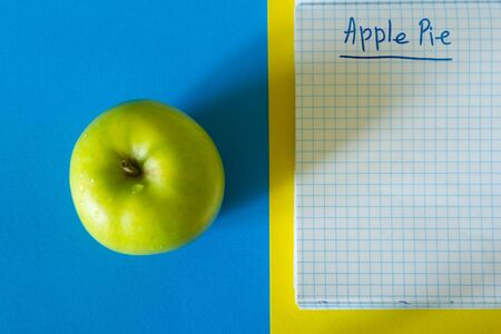 Green apple with notepad. Copy space for recipe