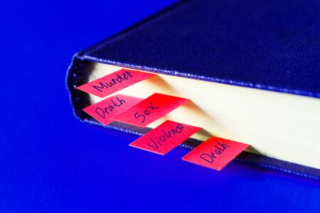 Book with many bookmarks inside it on blue background