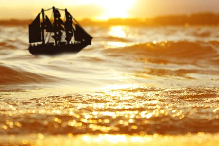 Silhouette of sailing ship, sunset background
