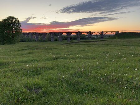 meadow with green grass and Old railroad bridge in the distance
