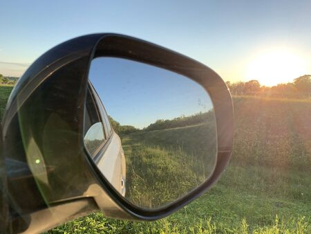 Travel by car concept. Side view mirror. Green field