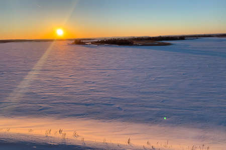 Sunset over the field covered with snow