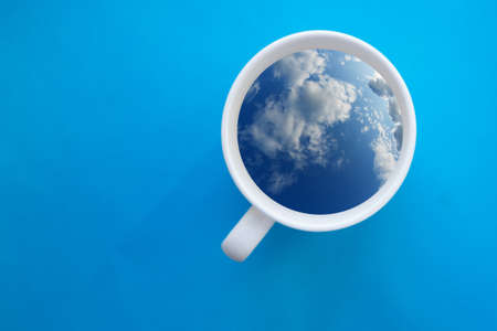 Coffee cup in shape of balloon with clouds on blue paper background.