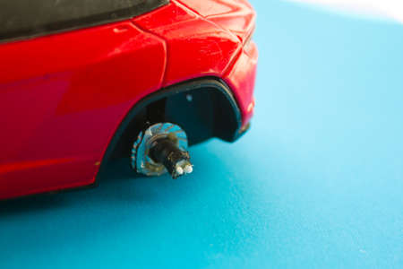 Red toy car without a wheel. Car service concept