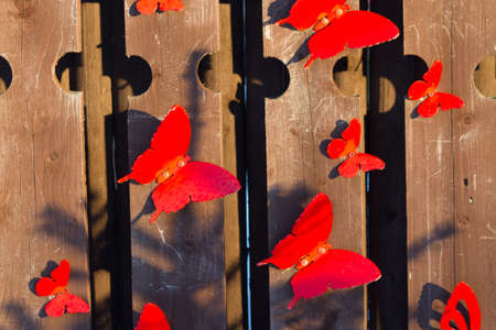 Red butterfly decoration on wooden fence