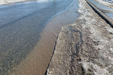 Snow melting on a road. Spring in the city