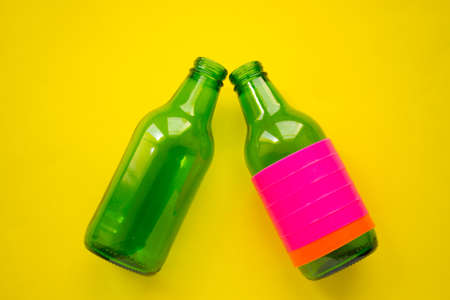 Green beer bottle on yellow background