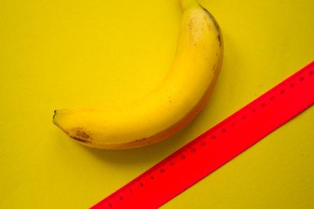Large banana and measuring tape. Size concept Zdjęcie Seryjne
