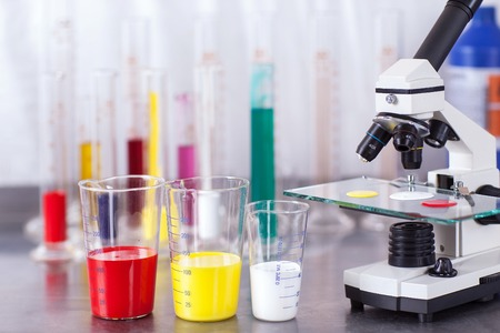 laboratory microscope with paints. Red, yellow and white Stock Photo