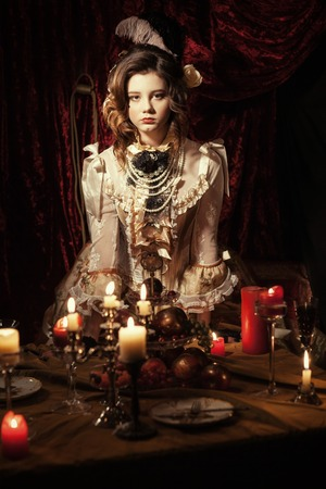 navarra: Portrait of a girl in old-style on a dark background. He is standing at the table with candles Stock Photo