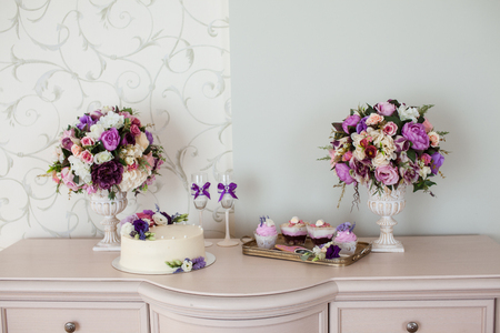 chest of drawers: Wedding decorations. Bouquets of flowers and cake on the chest of drawers