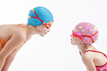 Two girls in swimming suits look at each other