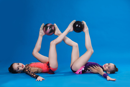 Two caucasian gymnasts with a ball