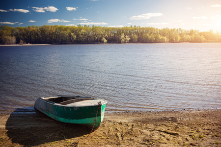 edges: An old boat on the shore of the pond