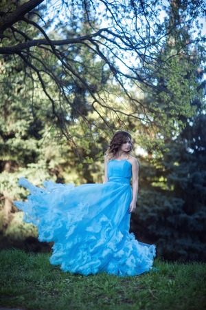 Young beautiful girl in a lush blue dress