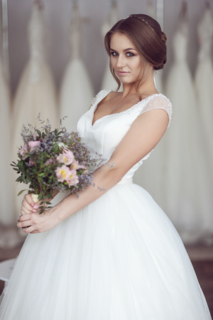 Bride in the background of a hanger with wedding dresses Stock Photo