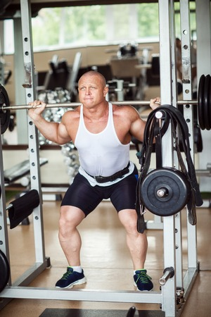 The man crouches with a barbell