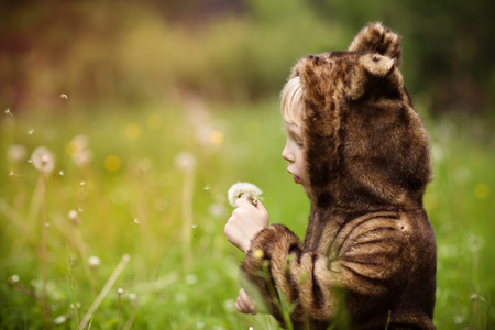 Little girl in a bear costume in the summer outdoors Stock Photo